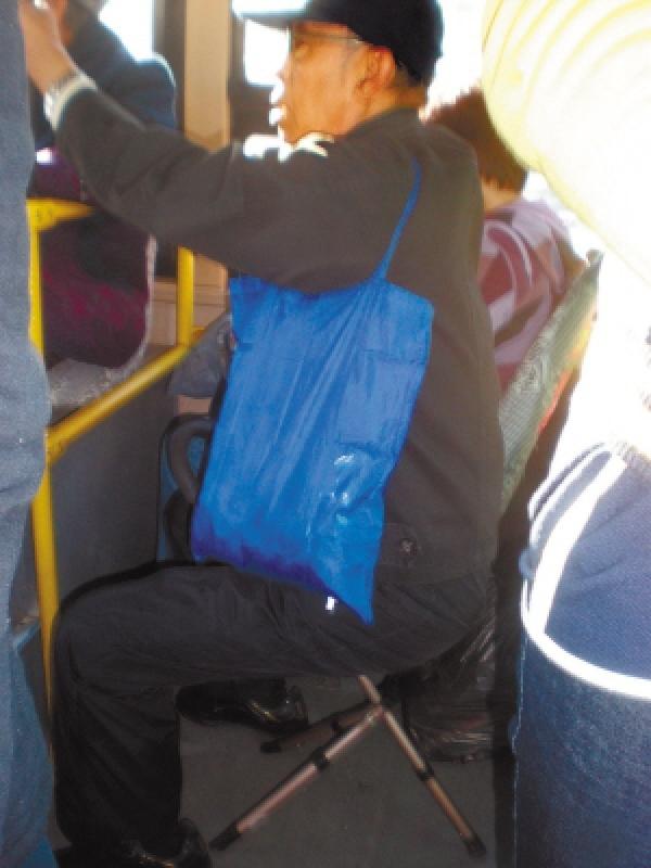 哈尔滨7旬老人坐公交怕麻烦别人自带 小马扎高清图片
